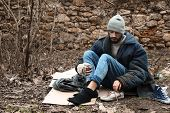 Poor Homeless Man Sitting On Cardboard In City Park poster