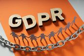 Wooden GDPR letters in front of human paper figures and metal chain. General data protection concept poster