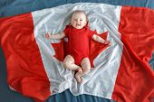White Caucasian Smiling Baby Boy Girl With Blue Eyes Lying On Large Canadian Flag With Red Maple Lea poster