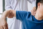 Doctor Physiotherapist Assisting A Male Patient While Giving Exercising Treatment Massaging The Shou poster