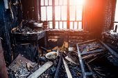 Burnt House Interior. Burned Kitchen, Remains Of Furniture In Black Soot. poster