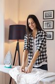 Woman Folding Clean Ironed Shirt On The Ironing Board After Doing The Ironing poster