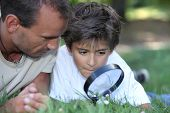 stock photo of dimples  - father and kid with magnifying glass - JPG
