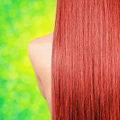 Straight long red hair on green bokeh background