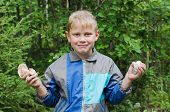 foto of face-fungus  - The joyful boy shows mushrooms which has found - JPG