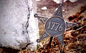 picture of revolutionary war  - bronze star that sits in the ground by a grave stone - JPG
