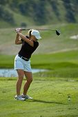 stock photo of ladies golf  - A female golfer swings a driver on the tee box - JPG