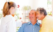 stock photo of hospice  - Happy elderly couple talking with their carer - JPG