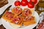 plate of bread with tomatoes and jamon