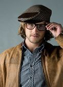 stock photo of beret  - Portrait of a handsome caucasian man wearing a leather jacket blue checkered button shirt beret and retro glasses - JPG