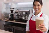 Happy young barista offering cup of coffee to go smiling at camera in a cafe
