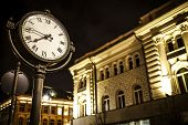 stock photo of tenement  - The photo presents a fragment of the night illuminated street with tenement building in th background and lit old tyle street clock in the front.