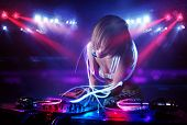 foto of disc jockey  - Pretty young disc jockey girl playing music with light beam effects on stage - JPG