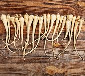 stock photo of parsnips  - Closeup of a bunch of parsnip on a wooden board - JPG