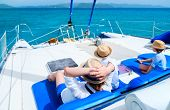 stock photo of boat  - Back view of mother and her kids relaxing having great time sailing at luxury yacht or catamaran boat - JPG