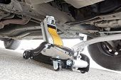 foto of hydraulics  - Garage hydraulic jack lifting up an automobile. ** Note: Soft Focus at 100%, best at smaller sizes - JPG