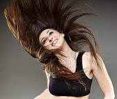 stock photo of hair motion  - Young woman dancing with her long hair fluttering in motion isolated on white - JPG