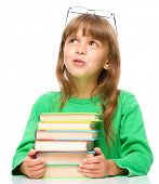 image of daydreaming  - Young girl is daydreaming while reading book and wearing glasses - JPG