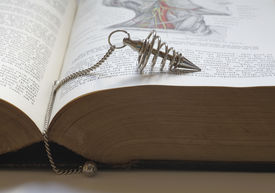picture of wicca  - Spiral dowsing pendant sitting on an old medical book open at a page showing a neck diagram - JPG