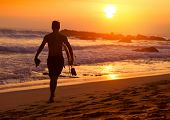 stock photo of board-walk  - Surfer walking with the board along sandy beach at sunset - JPG