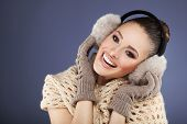 image of muffs  - Winter woman with ear muff posing in studio - JPG