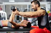 stock photo of sportive  - Personal fitness trainer assisting a young woman in the gym at a workout - JPG
