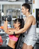 picture of personal assistant  - Personal fitness instructor helping a young woman doing workout with dumbbells - JPG