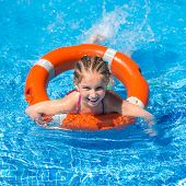 image of lifeline  - smiling little girl swims with a lifeline in the pool in  summer - JPG