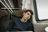 picture of passenger train  - Young man sleeping while traveling on a train sitting in a passenger coach with his head resting on his hand and eyes closed - JPG