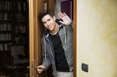 stock photo of peer  - Smiling young man getting out of door waving at the camera with a friendly cheerful smile as he peers around the edge of a wooden door - JPG