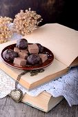 image of truffle  - Chocolate truffles on old books with vintage lace on wooden table - JPG