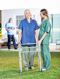 stock photo of zimmer frame  - Female nurse helping senior woman to use walking frame in lawn with caretaker in background at nursing home - JPG