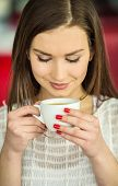 picture of pullovers  - Young beautiful girl in white pullover sitting in urban cafe with a cup of coffee - JPG