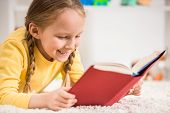 pic of pullovers  - Little pretty girl in yellow pullover reading book on colorful background - JPG