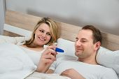 image of pregnancy test  - Happy Couple Watching Pregnancy Test In Bedroom - JPG