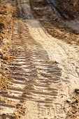 foto of wheel loader  - wheel track and foot print on clay road - JPG