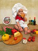 picture of boys  - Baby boy dressed as a cook boy sitting on the table with food for pizza baby  - JPG