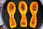 image of butternut  - Three butternut squash pieces with pumpkin seeds on black tray topview - JPG