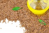 foto of flax seed oil  - Macro view of flax seeds and glass bottle of oil with green leaves - JPG