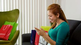 stock photo of post-teen  - Young latina woman back at home after shopping surrounded by bags on sofa - JPG