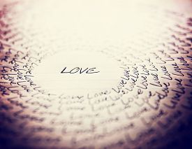 image of cursive  - the word love written on a lined piece of school paper in ink with a vignette and a circle of love  - JPG