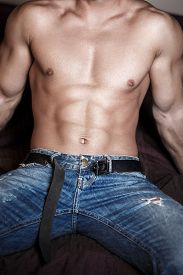 foto of packing  - Sexy man body sit on bed six pack abs - JPG
