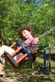 Girl Swinging On Swing Happy In Trees Outdoor