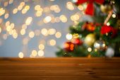holidays, new year and celebration concept - close up of empty wooden surface or table over christma poster