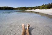 stock photo of mckenzie  - mans feet and legs lying in lake mckenzie - JPG