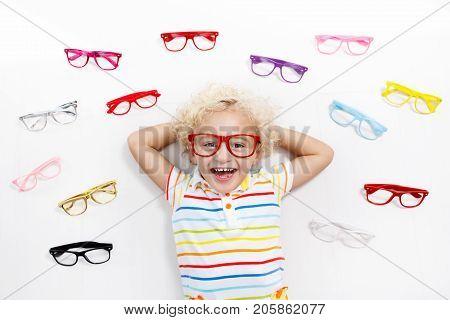 d975861e5e Kid At Optitian. Eyewear For Kids. Child at eye sight test. Little kid  selecting glasses at optician store. Eyesight measurement ...