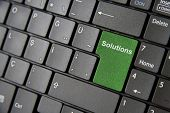 picture of backspace  - A close up to a laptop keyboard which has a green solution key - JPG