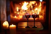 Two Glasses Of Red Wine Near Fireplace poster