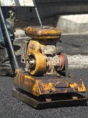 image of vibration plate  - Old worn little compactor plate in use on tarmac - JPG