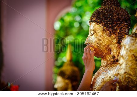 poster of Thai People Make Merit, Buddhists Gilding Gold Leaf On The Face Of Buddha Statue To Worship Buddha I